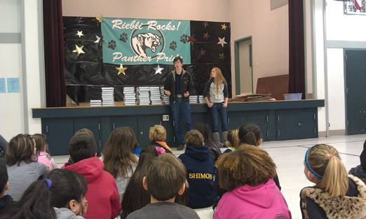 Cardinal Newman Interact members Paige Amormino and  Josh Gluch demonstrate the learning advantages of owning your own dictionary to young students at Riebli Elementary School