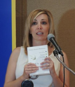 Carrie Ludke holds the book written by her guest and today's speaker, Ginny Scales-Mederios