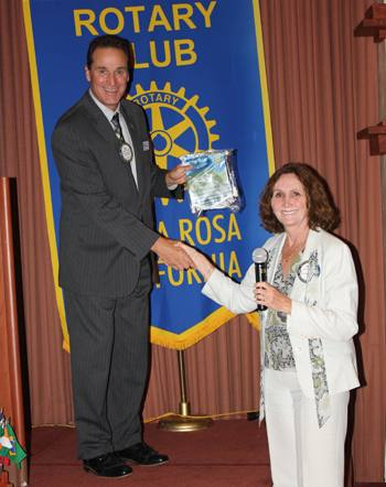 President Bill accepts the Honolulu Rotary flag from Jackie McMillan