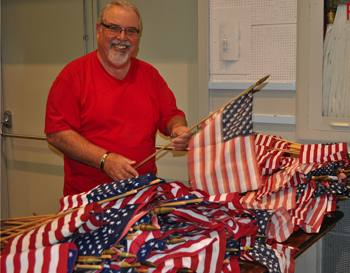Ray Dorfman prepares flags for decorations