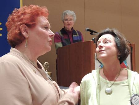 Debi Zaft sings Happy birthday while Ginny Cannon listens