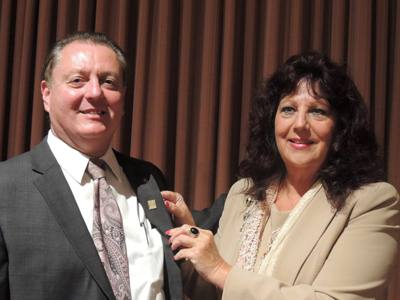Donna Lee gives Doug Johnson a Rotoplast pin