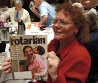 Debi Zaft showing the cover of this month's Rotarian magazine