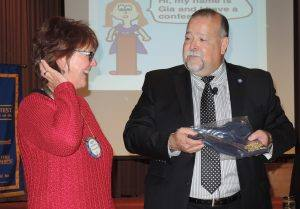 Rotarian of the Month - Kathy Schwartz. President Jose presenting a Rotary t-shirt and gift certificate