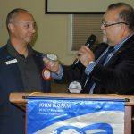President Jose presenting a blue badge to Matthew Henry