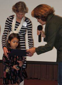 Judy Glenn's granddaughter receiving her Paul Harris certificate from Kim Graves.