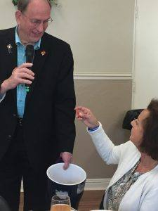 Rotarian Dan Balfe holds the raffle bucket and Ginny Cannon pulls the lucky number
